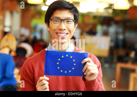 Happy young asian student holding flag of europe union - Stock Photo