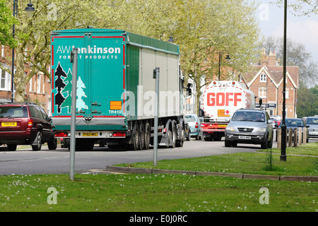 Articulated trucks and cars traveling passed parked cars on the A28 road in the rural town of Tenterden in Kent, - Stock Photo