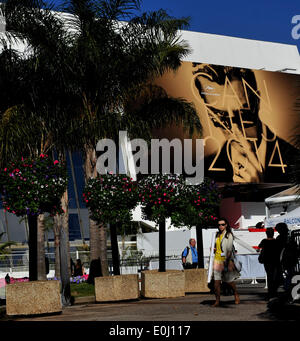 Cannes, France. 14th May, 2014. People walk past a giant poster of the 67th Cannes Film Festival in Cannes, France, May 14, 2014. The 67th Cannes Film Festival will run from May 14 to 24 with 18 films competing for the top prize the Palme d'Or. Credit:  Chen Xiaowei/Xinhua/Alamy Live News