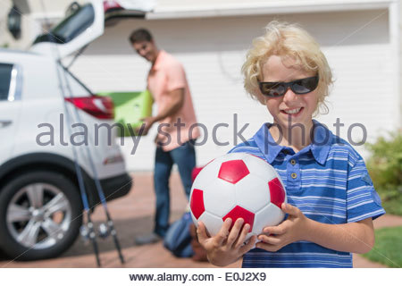 Portrait of smiling boy holding soccer ball in sunny driveway - Stock Photo