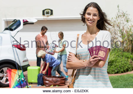 Portrait of smiling woman holding passports in driveway with family packing car in background - Stock Photo