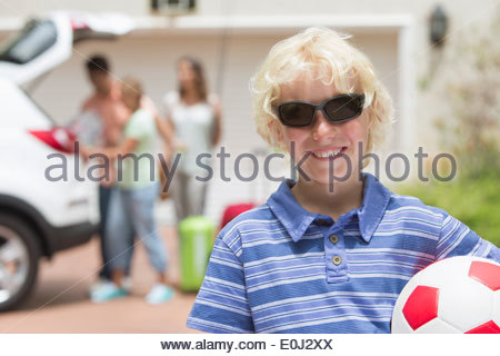 Portrait of smiling boy in sunglasses holding soccer ball in sunny driveway - Stock Photo