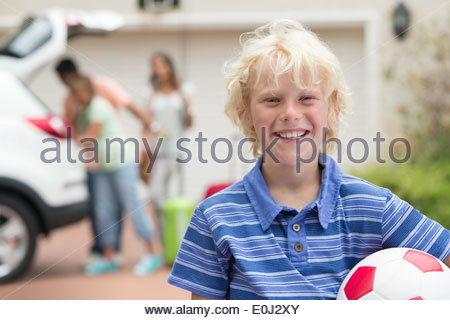 Portrait of smiling boy holding soccer ball in driveway - Stock Photo
