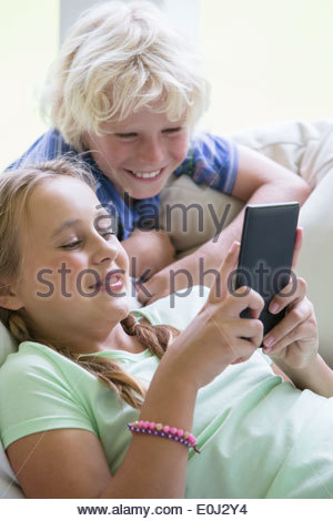 Smiling brother and sister using digital tablet on sofa - Stock Photo