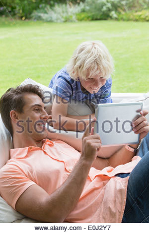 Smiling father and son using digital tablet on outdoor sofa - Stock Photo