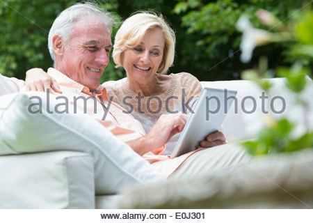 Senior couple using digital tablet on outdoor sofa - Stock Photo