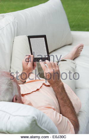 Senior man laying on outdoor sofa and using digital tablet - Stock Photo