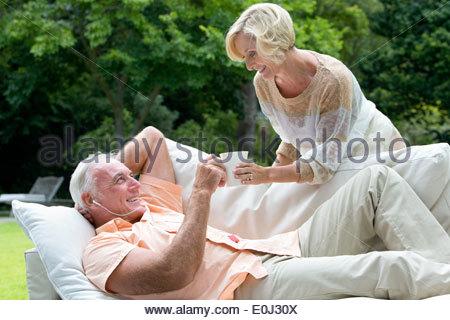 Senior woman bringing coffee to man with headphones on outdoor sofa - Stock Photo