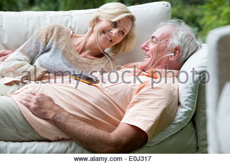 Senior couple listening to music on shared headphones on outdoor sofa - Stock Photo