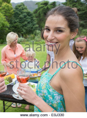 Portrait of smiling woman drinking wine near barbecue - Stock Photo