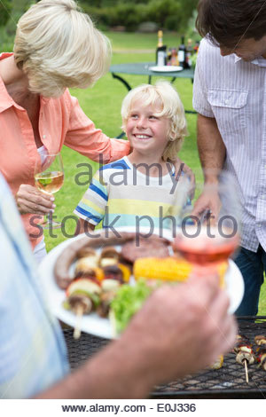 Happy multi-generation family enjoying barbecue and wine - Stock Photo