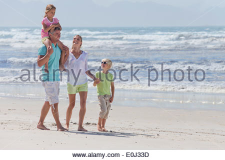 Family walking on sunny beach - Stock Photo