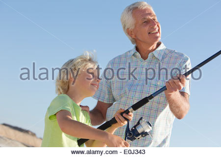 Grandfather and grandson fishing on sunny beach - Stock Photo