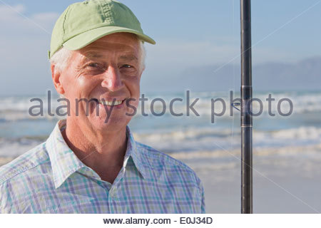 Close up portrait of smiling senior man with fishing rod on sunny beach - Stock Photo