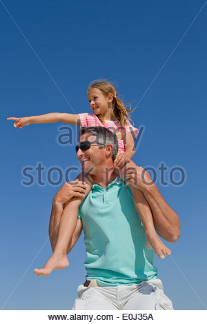 Father carrying daughter on shoulders against blue sky - Stock Photo