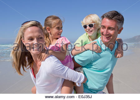 Parents piggybacking children on sunny beach - Stock Photo