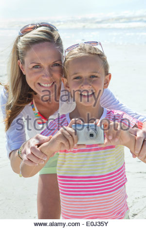 Portrait of smiling mother and daughter with digital camera on sunny beach - Stock Photo