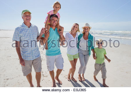 Portrait of smiling multi-generation family walking on sunny beach - Stock Photo