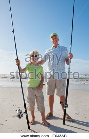 Portrait of grandfather and grandson with fishing rods on sunny beach - Stock Photo