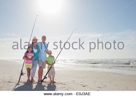 Portrait of grandparents and grandchildren with fishing rods on sunny beach - Stock Photo