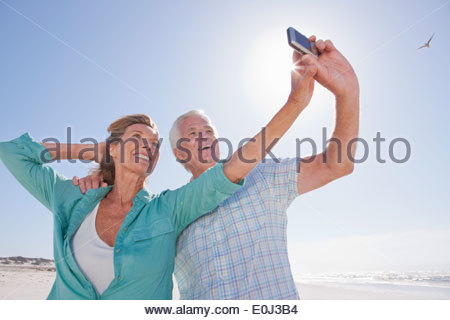 Senior couple with digital camera taking self-portrait on sunny beach - Stock Photo