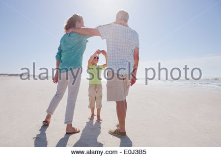 Grandparents and grandson on sunny beach - Stock Photo