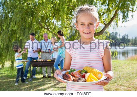 Multi-Generation Family Enjoying Barbeque By Lake - Stock Photo