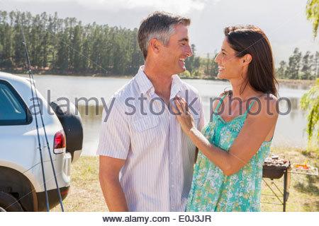 Couple Enjoying Barbeque By Lake - Stock Photo
