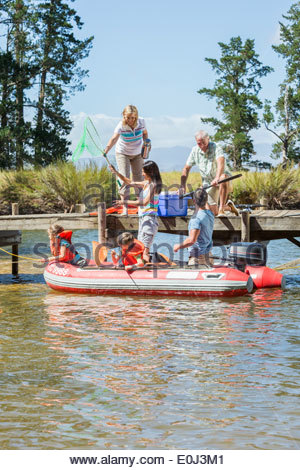 Multi-Generation Family Enjoying Boat Trip On Lake - Stock Photo
