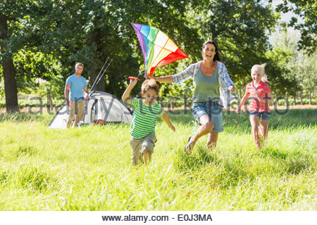 Family Flying Kite Camping Holiday In Countryside - Stock Photo
