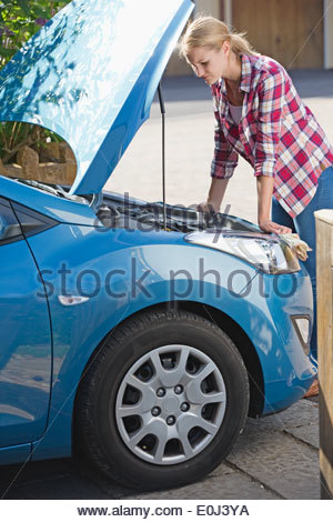 Woman With Broken Down Car Looking Under Bonnet - Stock Photo