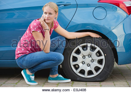 Woman With Flat Tyre On Car Phoning For Assistance - Stock Photo