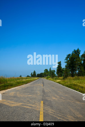 Long road stretching out into the distance under a dramatic blue sky