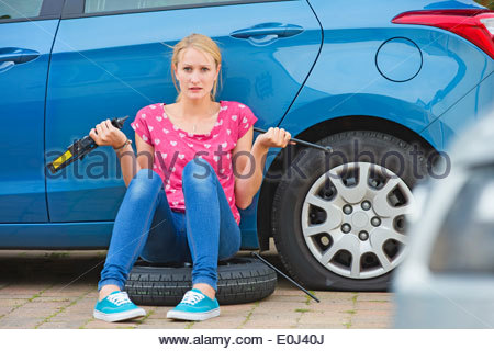 Frustrated Woman Trying To Change Flat Tyre On Car - Stock Photo