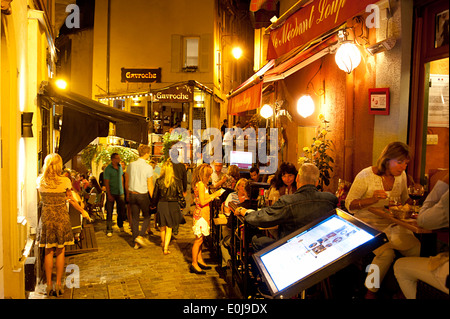 Tourists visit local cafes and restaurants in Cannes old city center. - Stock Photo