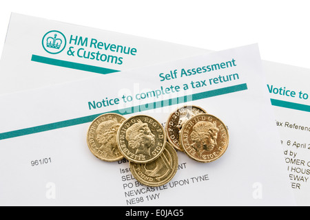 UK HM Revenue & Customs Self Assessment Notice to complete a tax return with some pound coins on white. England - Stock Photo
