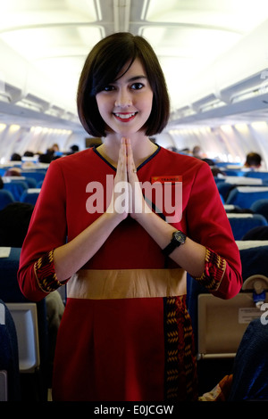 air hostess at work on board a sriwijaya air domestic flight en route from malang to jakarta java indonesia - Stock Photo