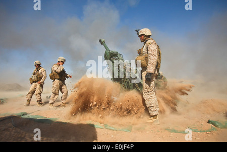 An M777 howitzer kicks rocks and dust into the air after firing during a recent mission. The Marines with Charlie - Stock Photo