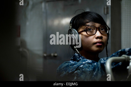 Seaman Mafe Sabar mans a sound-powered telephone inside the aft steering engine room aboard the Nimitz-class aircraft - Stock Photo