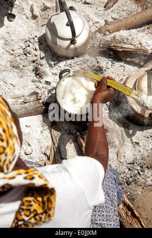 Kavango woman preparing the traditional maize flour dish Ugali or Pap on the open fire, Okavango Delta, Botswana, - Stock Photo