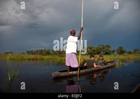 Poler on their traditional mokoro boat in the Okavango Delta, Botswana, Africa - Stock Photo