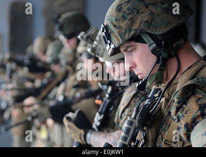 Marines assigned to the 31st Marine Expeditionary Unit, Maritime Raid Force, check their weapons during a call-away - Stock Photo