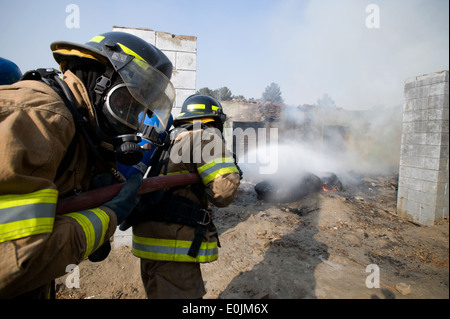 KABUL, Afghanistan --Members of the Afghan National Air Corps fire protection unit respond a fire intentionally - Stock Photo