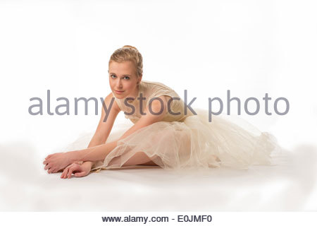 Teen girl in a white tutu on a white background sitting on the floor stretching. - Stock Photo