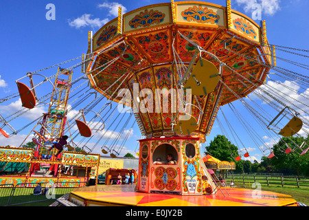 Girl taking a ride on the swing carousel at  the Royal Windsor Horse Show,Windsor, Berkshire, - Stock Photo