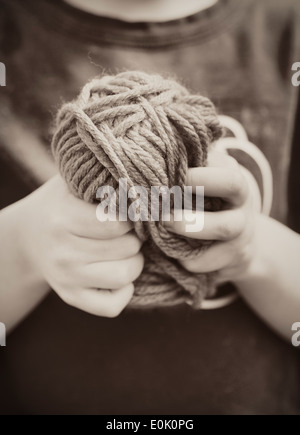 Close up of little girl holding a ball of yarn in her hands - Stock Photo
