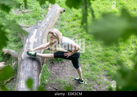Blonde lady wearing black leggings and a grey crop stretching her leg on a log on hampstead heath. - Stock Photo