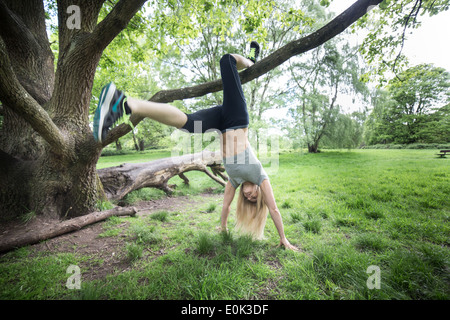 Blonde lady wearing black leggings and a grey crop exercising on hampstead heath. - Stock Photo