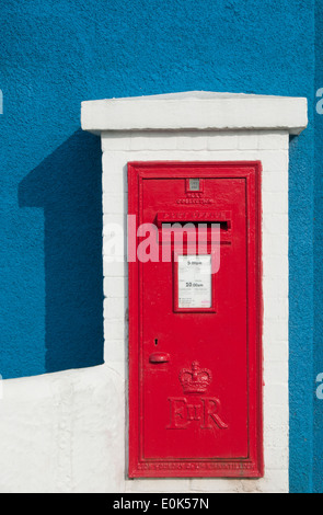 Bright Red Post Box on Bright Blue Painted Wall, Isle of Anglesey, North Wales, UK - Stock Photo