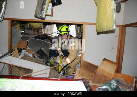 A member of the Fairfax County Urban Search and Rescue Team pushes aside furniture and ruble while looking for survivors, - Stock Photo